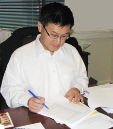 Controller John Chiang reviewing and signing a Controller's audit report